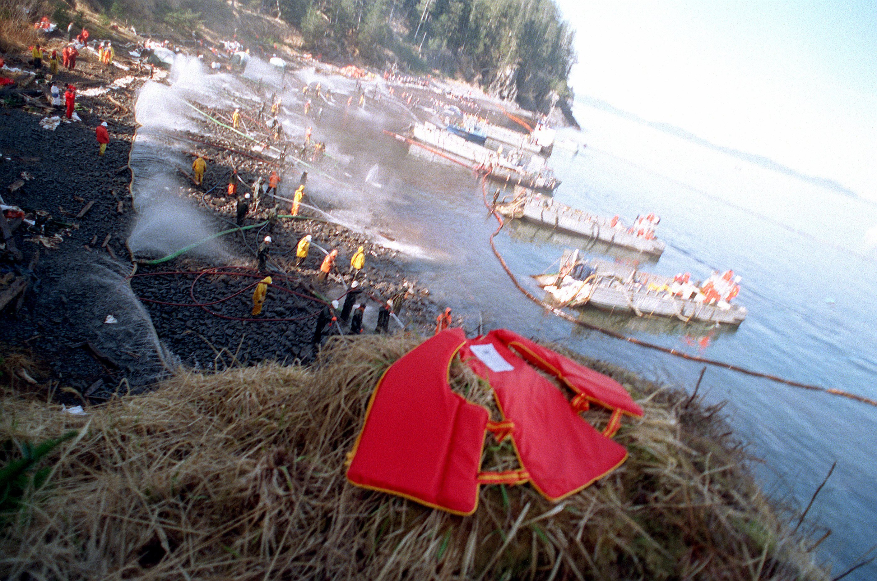U.S. Navy Mechanized Landing Craft (LCMs) are anchored along the shoreline as Navy and civilian personnel position hoses during oil clean-up efforts on Smith island. The massive oil spill occurred when the commercial tanker Exxon Valdez ran aground while transiting the waters of Prince William Sound on March 24th.