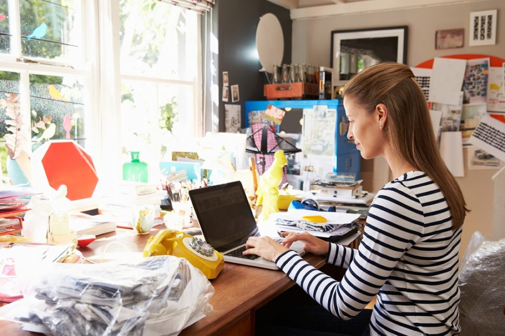 Woman sitting in a cluttered creative space programming away